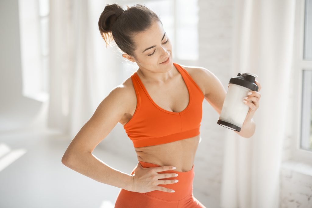 Sports woman with protein shaker at gym