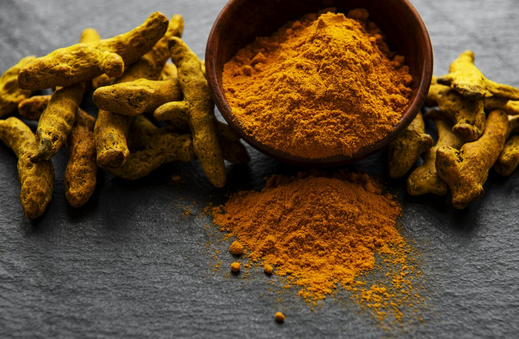 Yellow turmeric powder and dry roots